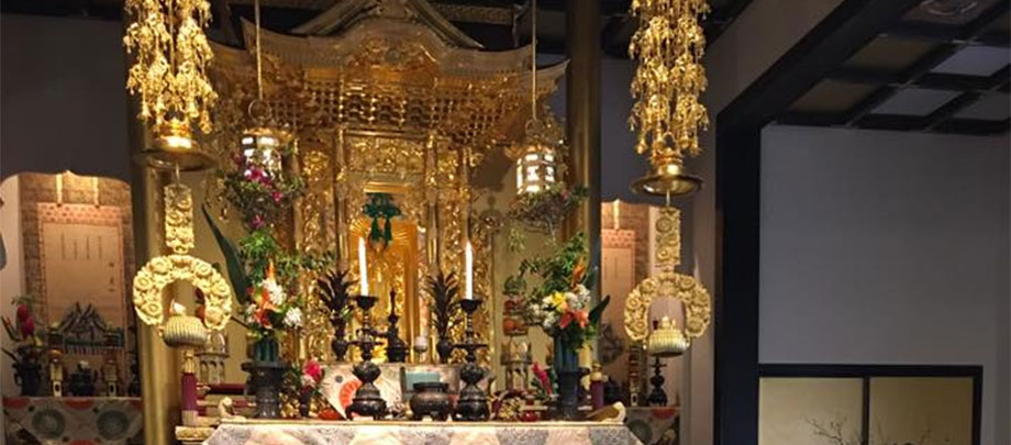 altar area at Moiliili Hongwanji Mission (image of Amida Buddha, guilded lanterns and ornamentation, candles, flowers)