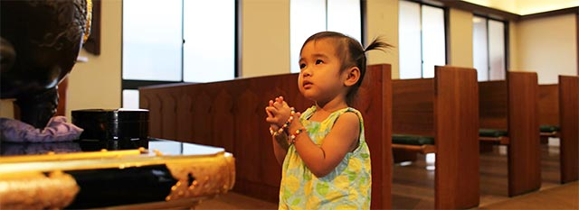little girl with hands together approaches altar area