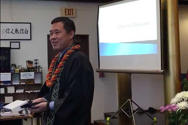 Blayne Higa, in robes and wearing lei, speaks at Moiliili Hongwanji