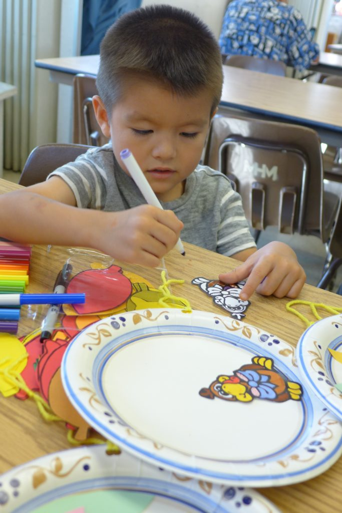 A Dharma School student making Thanksgiving decorations